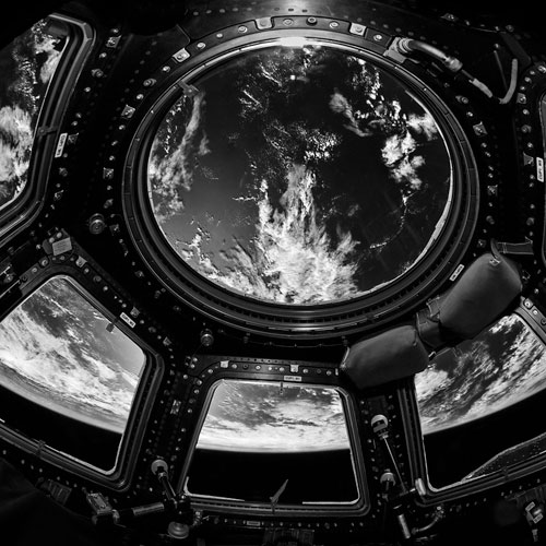The earth viewed through the cupola windows aboard ISS.